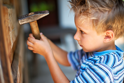 Little boy trying to hammer a nail